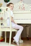 Bambina ad un pianoforte a coda bianco fotografia stock