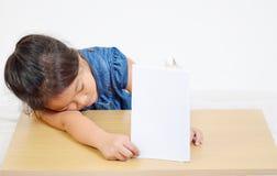 Bambina addormentata con il libro sulla tavola Fotografia Stock