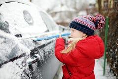 Bambina adorabile che contribuisce a spazzolare una neve da un'automobile Assistente del ` s della mamma piccolo fotografie stock libere da diritti