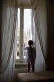 Bambina adorabile che esamina fuori la finestra Fotografie Stock