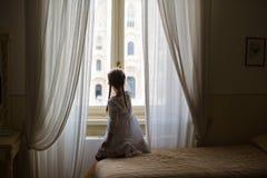 Bambina adorabile che esamina fuori la finestra Immagine Stock Libera da Diritti