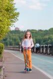 Bambina adorabile che guida il suo motorino in un parco di estate Fotografie Stock