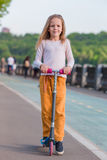 Bambina adorabile che guida il suo motorino in un parco di estate Fotografie Stock Libere da Diritti