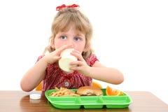 Bambina adorabile che ha pranzo al banco Immagine Stock