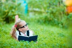 Bambina adorabile che legge un libro all'aperto Fotografie Stock Libere da Diritti
