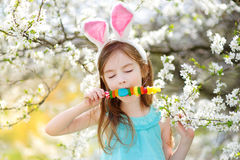 Bambina adorabile che mangia le caramelle variopinte della gomma su Pasqua Immagine Stock Libera da Diritti
