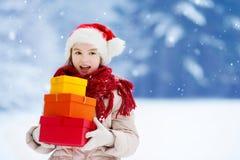 Bambina adorabile che porta il cappello di Santa che tiene un mucchio dei regali di Natale il bello giorno di inverno Fotografia Stock