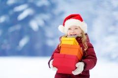 Bambina adorabile che porta il cappello di Santa che tiene un mucchio dei regali di Natale il bello giorno di inverno Fotografie Stock