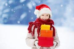 Bambina adorabile che porta il cappello di Santa che tiene un mucchio dei regali di Natale il bello giorno di inverno Fotografie Stock Libere da Diritti