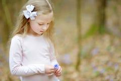 Bambina adorabile che seleziona i primi fiori della molla nel legno il bello giorno di molla soleggiato fotografia stock libera da diritti