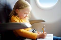 Bambina adorabile che viaggia in aeroplano Bambino che si siede dalla finestra degli aerei e che disegna un'immagine con i pennar Fotografie Stock Libere da Diritti
