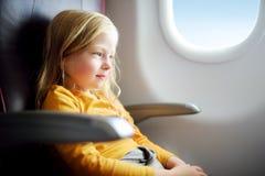 Bambina adorabile che viaggia in aeroplano Bambino che si siede dalla finestra degli aerei e che guarda fuori Fotografia Stock Libera da Diritti