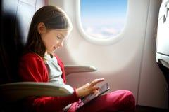 Bambina adorabile che viaggia in aeroplano Bambino che si siede dalla finestra degli aerei e che per mezzo di una compressa digit Immagine Stock Libera da Diritti