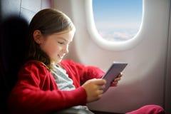 Bambina adorabile che viaggia in aeroplano Bambino che si siede dalla finestra degli aerei e che per mezzo di una compressa digit Fotografie Stock Libere da Diritti