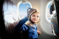 Bambina adorabile che viaggia in aeroplano Bambino che si siede dalla finestra e che gioca con l'aereo del giocattolo Immagine Stock