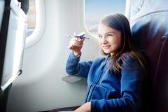 Bambina adorabile che viaggia in aeroplano Bambino che si siede dalla finestra e che gioca con l'aereo del giocattolo Immagini Stock Libere da Diritti