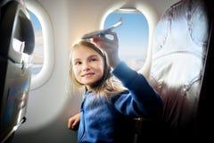 Bambina adorabile che viaggia in aeroplano Bambino che si siede dalla finestra e che gioca con l'aereo del giocattolo Fotografie Stock Libere da Diritti