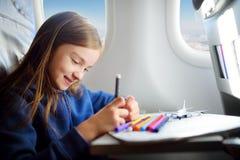 Bambina adorabile che viaggia in aeroplano Bambino che si siede dalla finestra e dal disegno Immagine Stock