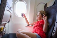 Bambina adorabile che viaggia in aeroplano Bambino che si siede vicino alla finestra degli aerei Immagini Stock