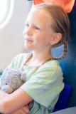 Bambina adorabile che viaggia in aeroplano Bambino che si siede vicino alla finestra degli aerei con l'orsacchiotto Immagini Stock Libere da Diritti