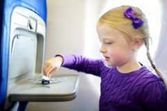 Bambina adorabile che viaggia in aeroplano Bambino che si siede dalla finestra degli aerei e che gioca con l'aereo del giocattolo Immagine Stock Libera da Diritti