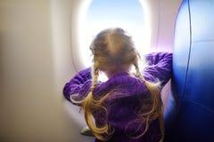 Bambina adorabile che viaggia in aeroplano Bambino che si siede dalla finestra degli aerei e che guarda fuori Fotografie Stock Libere da Diritti