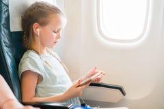 Bambina adorabile che viaggia in aeroplano Bambino sveglio con il computer portatile vicino alla finestra in aerei Fotografia Stock