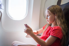 Bambina adorabile che viaggia in aeroplano Musica d'ascolto del bambino che si siede vicino alla finestra degli aerei Fotografie Stock