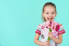 Bambina adorabile con il mazzo insolente della tenuta di espressione del fronte e di sorriso delle margherite rosa della gerbera  immagini stock libere da diritti