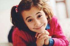 Bambina adorabile con il sorriso dolce che si riposa sul letto Fotografia Stock
