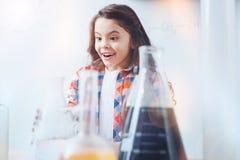 Bambina adorabile con la doppia presa durante la lezione di chimica Fotografia Stock