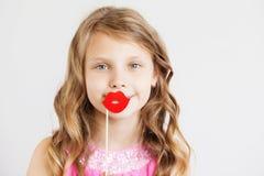 Bambina adorabile con le labbra di carta rosse divertenti contro un BAC bianco Immagini Stock