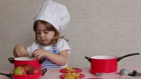 Bambina adorabile del ritratto in alimento del cuoco del cappello del cuoco unico video d archivio