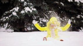 Bambina adorabile divertendosi il giorno di inverno all'aperto e giocando le palle di neve archivi video