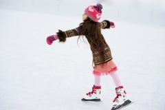 Bambina adorabile sulla pista di pattinaggio sul ghiaccio Fotografie Stock Libere da Diritti