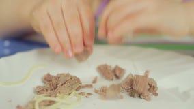 Bambina affascinante che mangia gli spaghetti con carne che tira alimento con le sue mani da un piatto archivi video