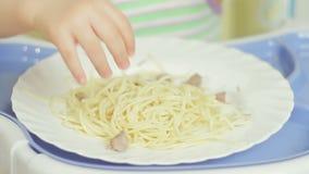 Bambina affascinante che mangia gli spaghetti con carne che tira alimento con le sue mani da un piatto video d archivio