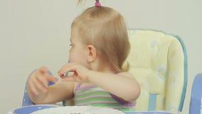 Bambina affascinante che mangia gli spaghetti con le sue dita e che lo gode archivi video
