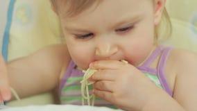 Bambina affascinante che mangia gli spaghetti con le sue dita e che lo gode video d archivio