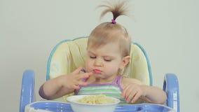 Bambina affascinante che mangia gli spaghetti con le sue dita e che lo gode stock footage