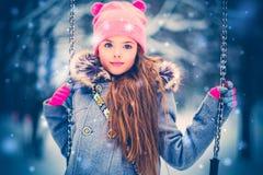Bambina affascinante su oscillazione nell'inverno nevoso immagine stock