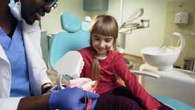 Bambina africana di insegnamento del dentista come pulire i denti sul modello di plastica archivi video