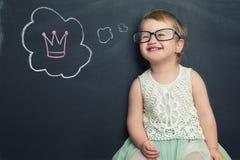 Bambina alla lavagna che pensa alla corona Fotografia Stock