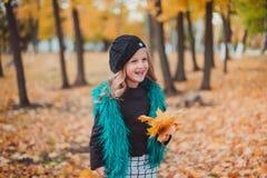 Bambina alle foglie della tenuta di autunno La bambina nel berretto marrone nel parco di autunno fotografia stock