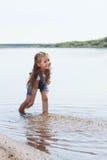 Bambina allegra che gioca nel lago immagine stock