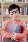 Bambina allegra con il libro che sorride sulla macchina fotografica Immagini Stock Libere da Diritti