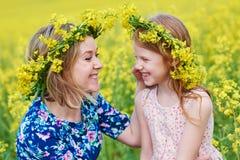 Bambina allegra della donna in ghirlanda del fiore al campo giallo fotografia stock libera da diritti
