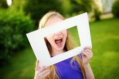 Bambina allegra sveglia che tiene la cornice bianca davanti al suo fronte Fotografie Stock Libere da Diritti