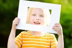 Bambina allegra sveglia che tiene la cornice bianca davanti al suo fronte Fotografie Stock