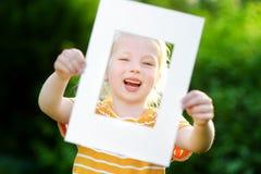 Bambina allegra sveglia che tiene la cornice bianca davanti al suo fronte Immagine Stock